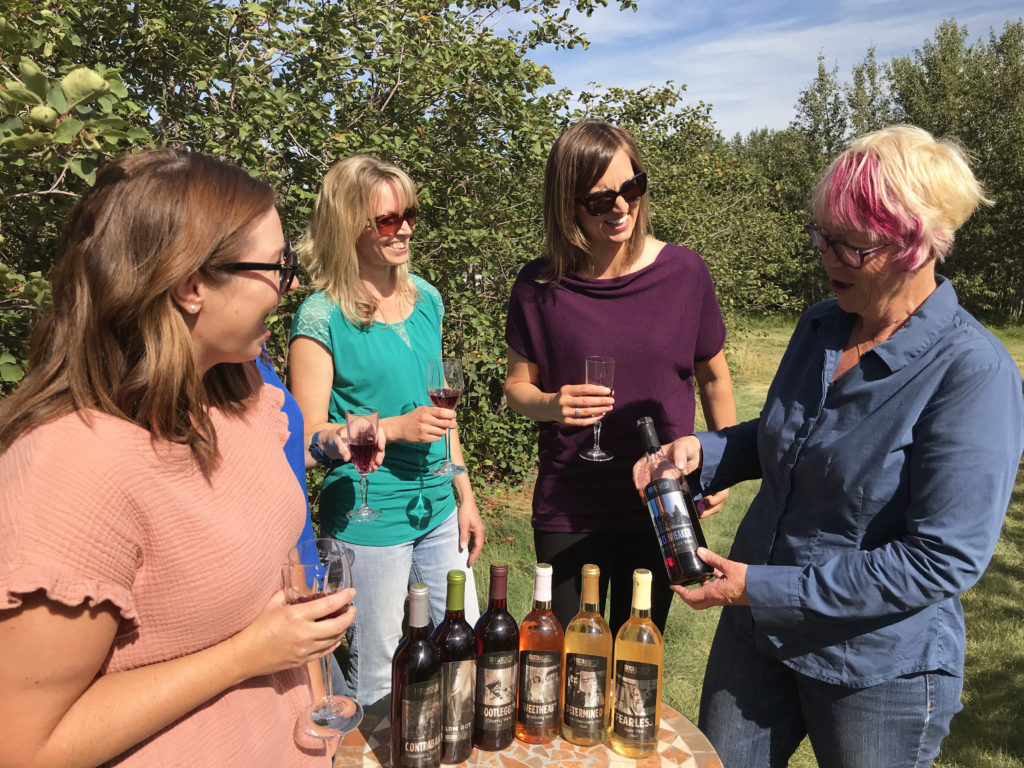 four women holding wine glasses standing beside a table of wines in an orchard
