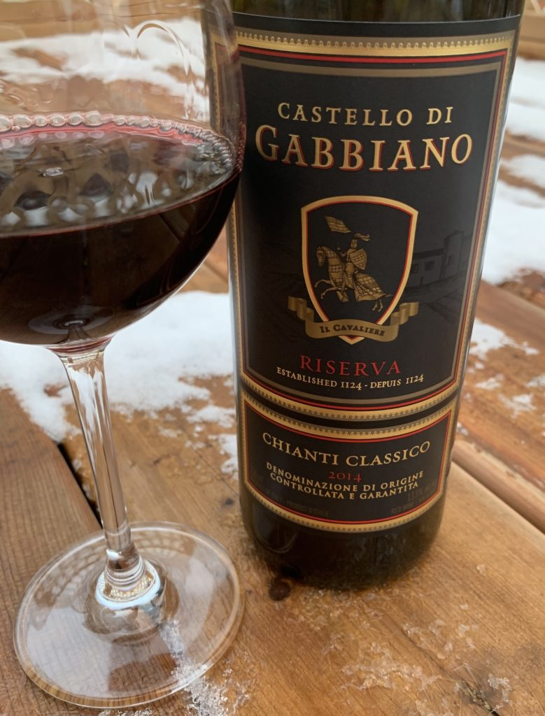 a glass of red wine sitting beside a bottle of Gabbiano Chianti Classico Riserva with snow in the background