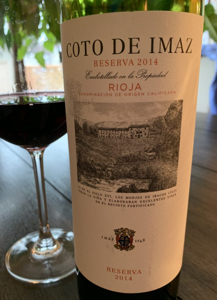 a glass of red wine sitting beside a bottle of Coto de Imaz Reserva Rioja