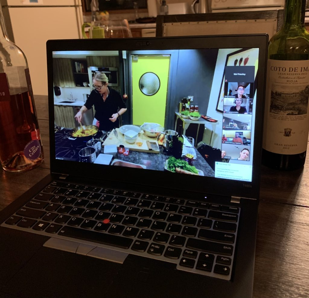 a laptop showing a cooking demonstration sitting on a table beside some wine bottles