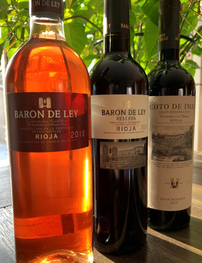 three bottles of Rioja wine from Baron de Ley with a green plant behind them