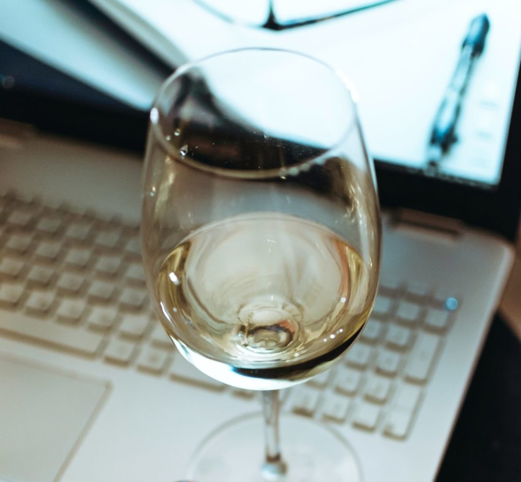 a glass of white wine sitting on the edge of an open laptop