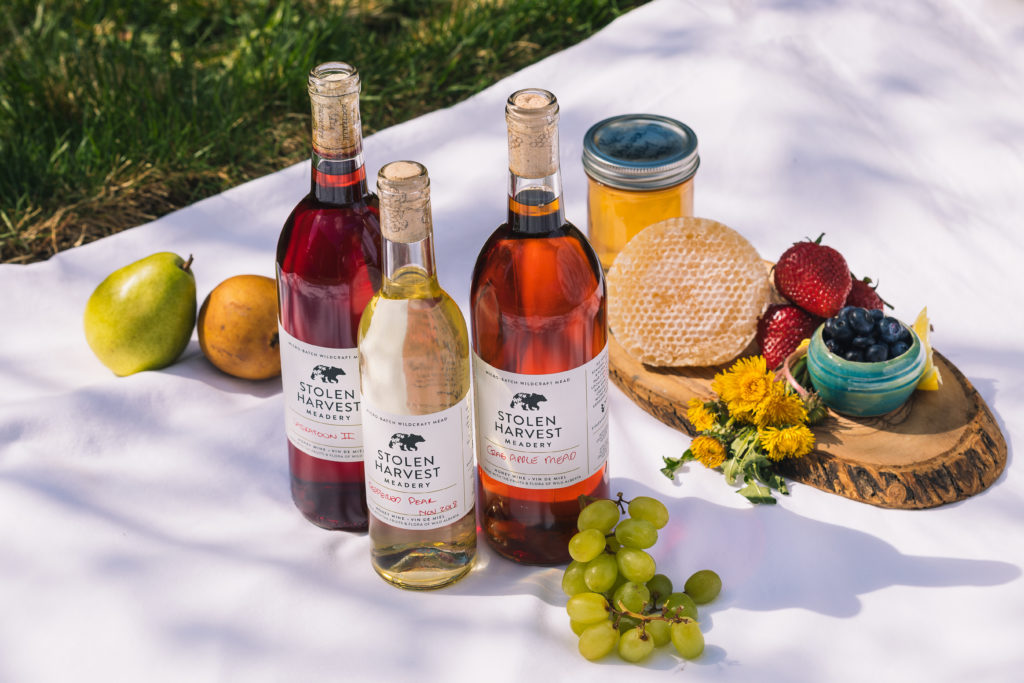 three bottles of wine on a white tablecloth with fruit and honeycomb behind